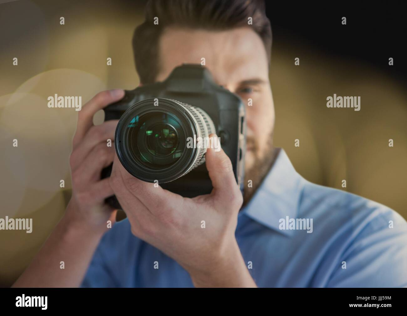 photographer foreground taking a photo. Blurred lights overlap - Stock Image