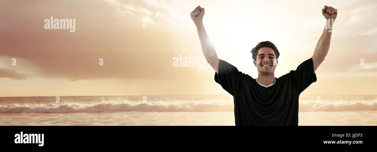 Man in jersey celebrating on sunset beach with flare - Stock Image