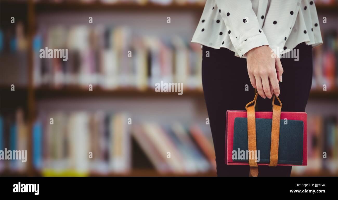 College student lower body against blurry bookshelf - Stock Image