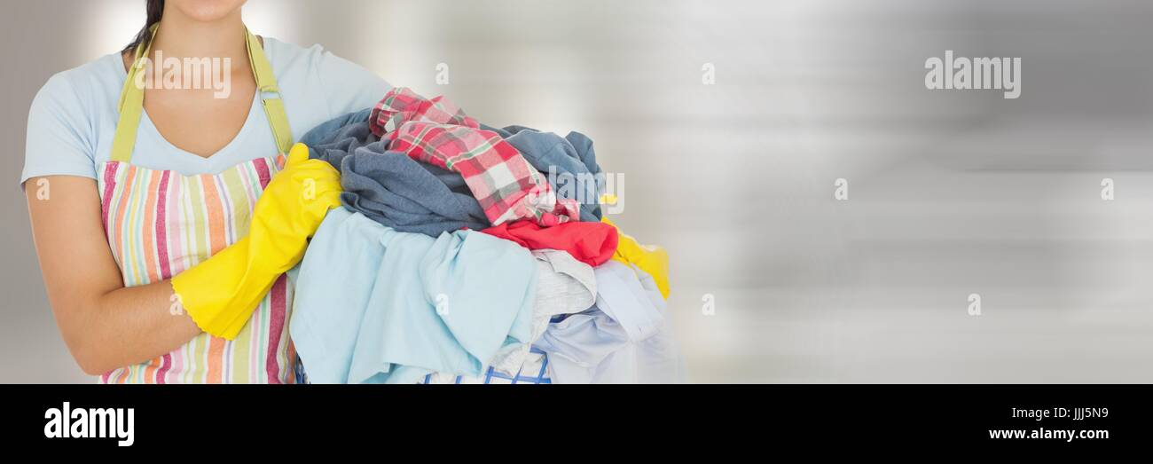 Cleaner holding laundry basket  with bright background - Stock Image