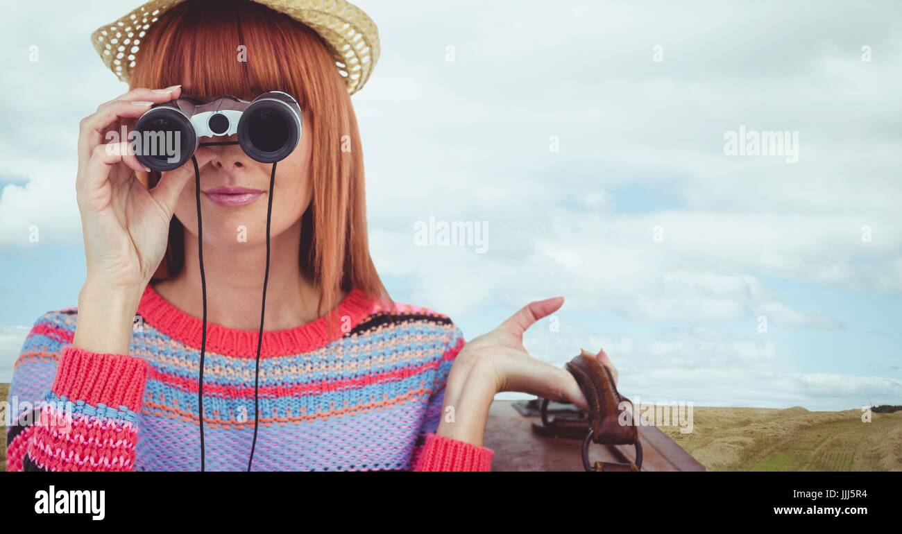 Woman looking through binoculars against landscape background Stock Photo