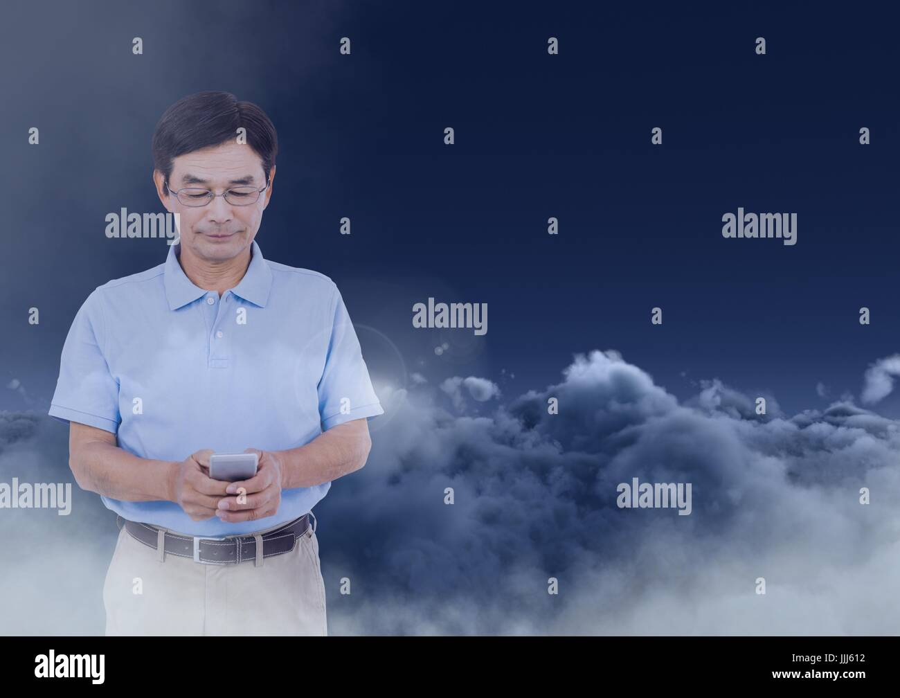 Man texting in darkness with clouds in background - Stock Image
