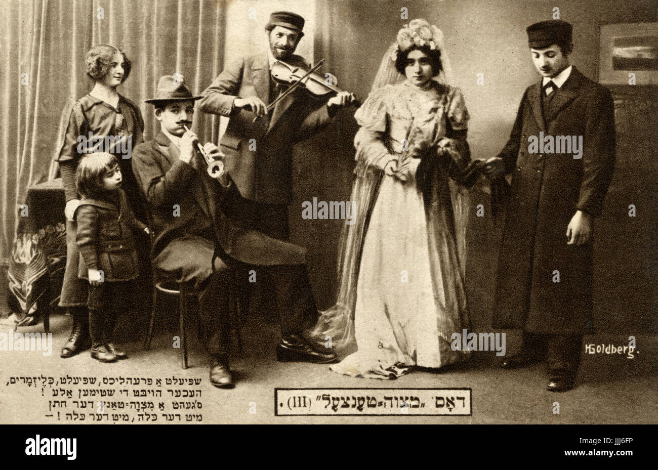 The Mitsva / mitzva Dance. Posed wedding scene with bride and groom and klezmer players. words of a wedding song - Stock Image