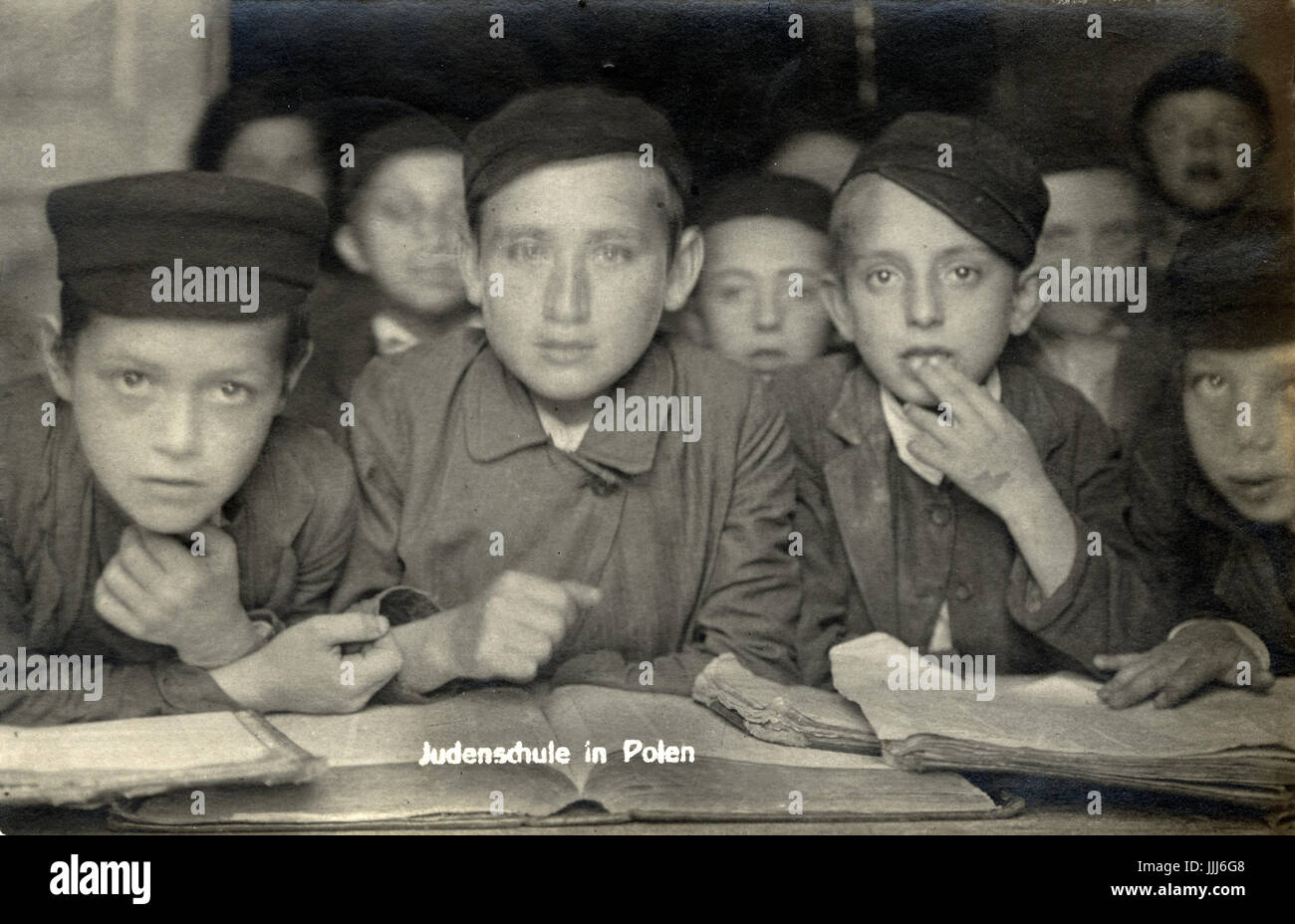 Schoolboys learning at Jewish religious  school / Cheder  in Poland  in 1916. Wearing caps. Field photo - taken - Stock Image