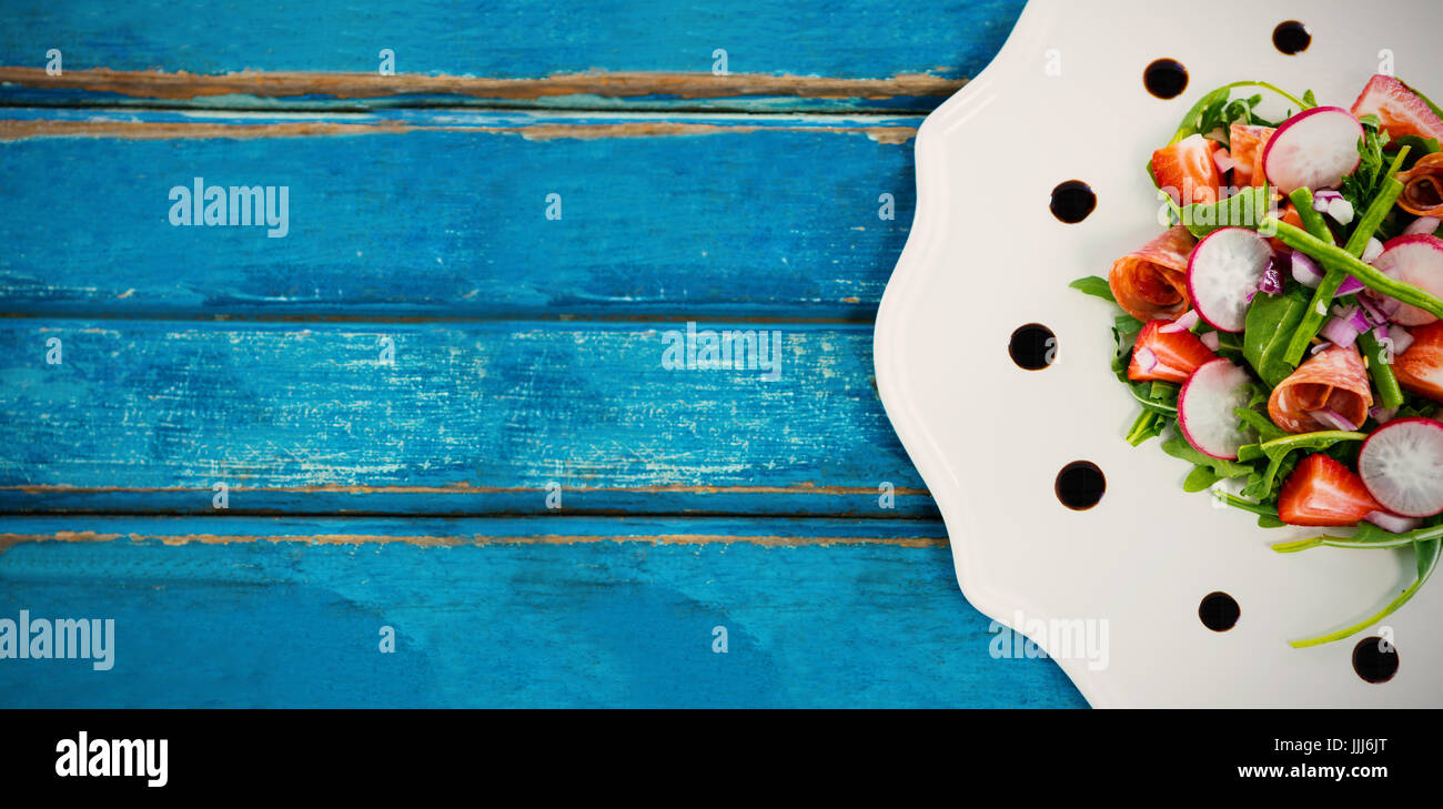 Fresh salad in plate served on blue table - Stock Image