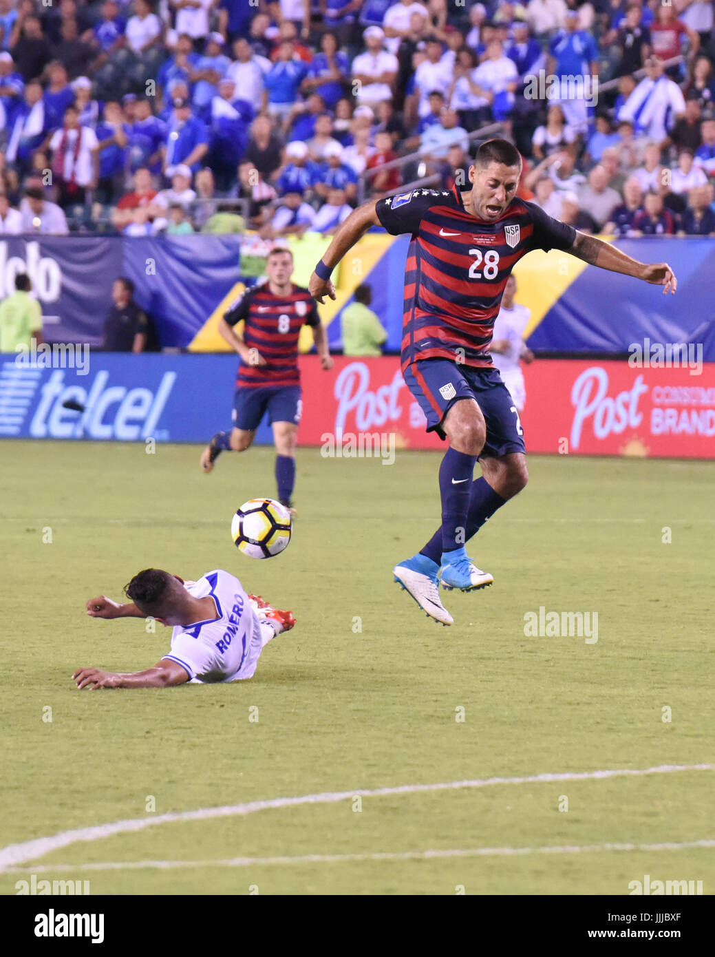 Clint Dempsey of the USMNT United States Mens National Team leaps over a tackle from Henry Romero during a soccer - Stock Image