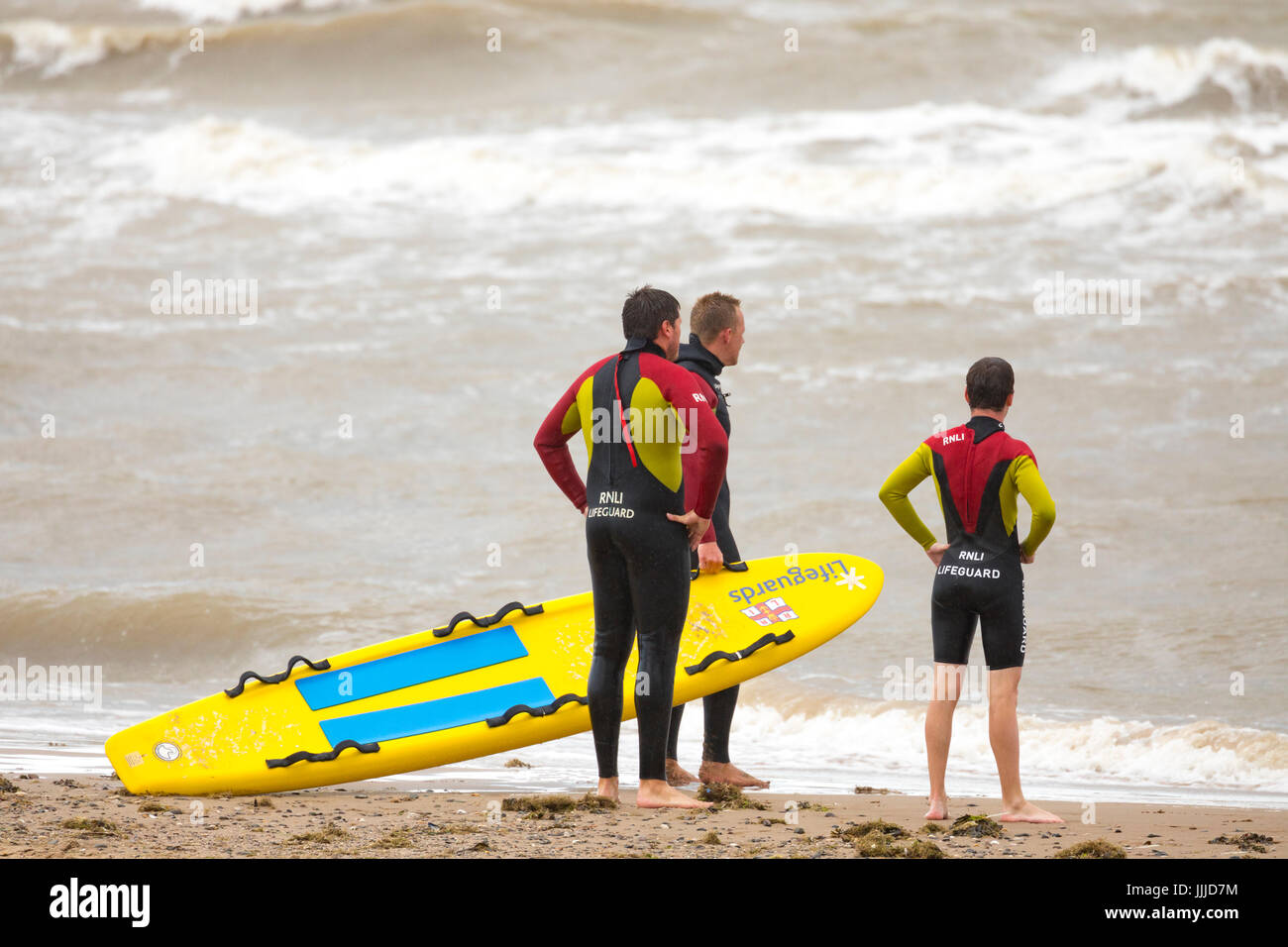Male lifeguards of the RNLI on the shore looking out to rough seas at the popular coastal resort of Rhyl in Denbighshire, Stock Photo