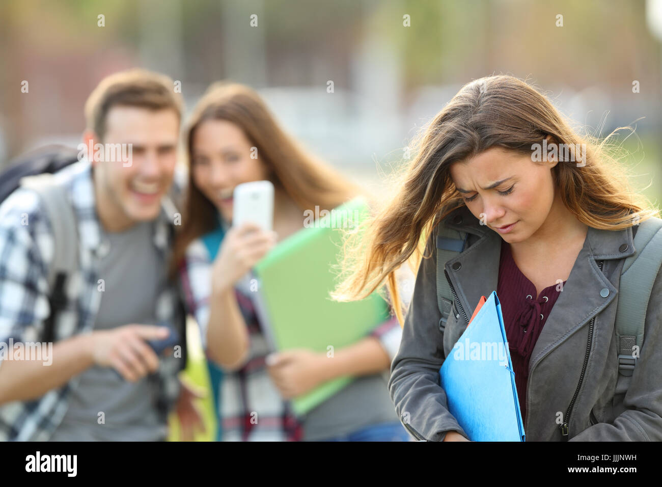 Bullying victim being video recorded on a smartphone by classmates in the street with a unfocused background - Stock Image