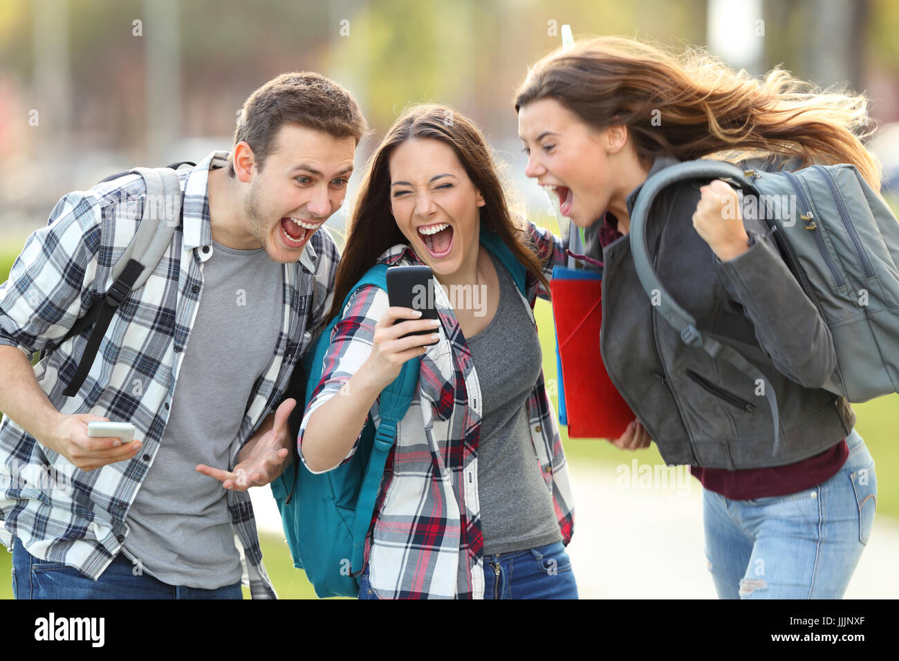 Front view of three excited students receiving good news on line in a mobile phone in an university campus or street - Stock Image