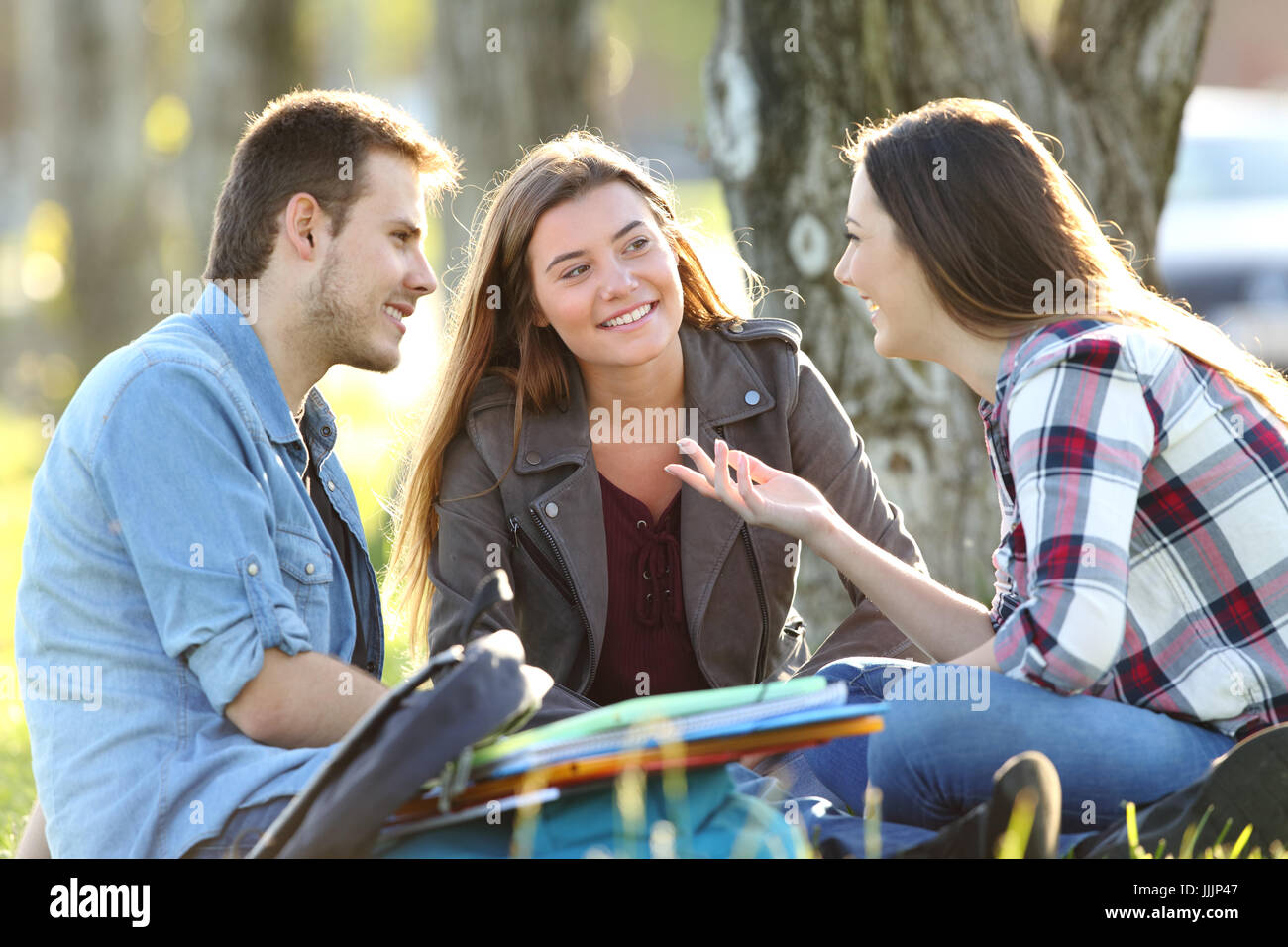 Three students talking after classes beside books and ruckpacks sitting on the grass in a park - Stock Image