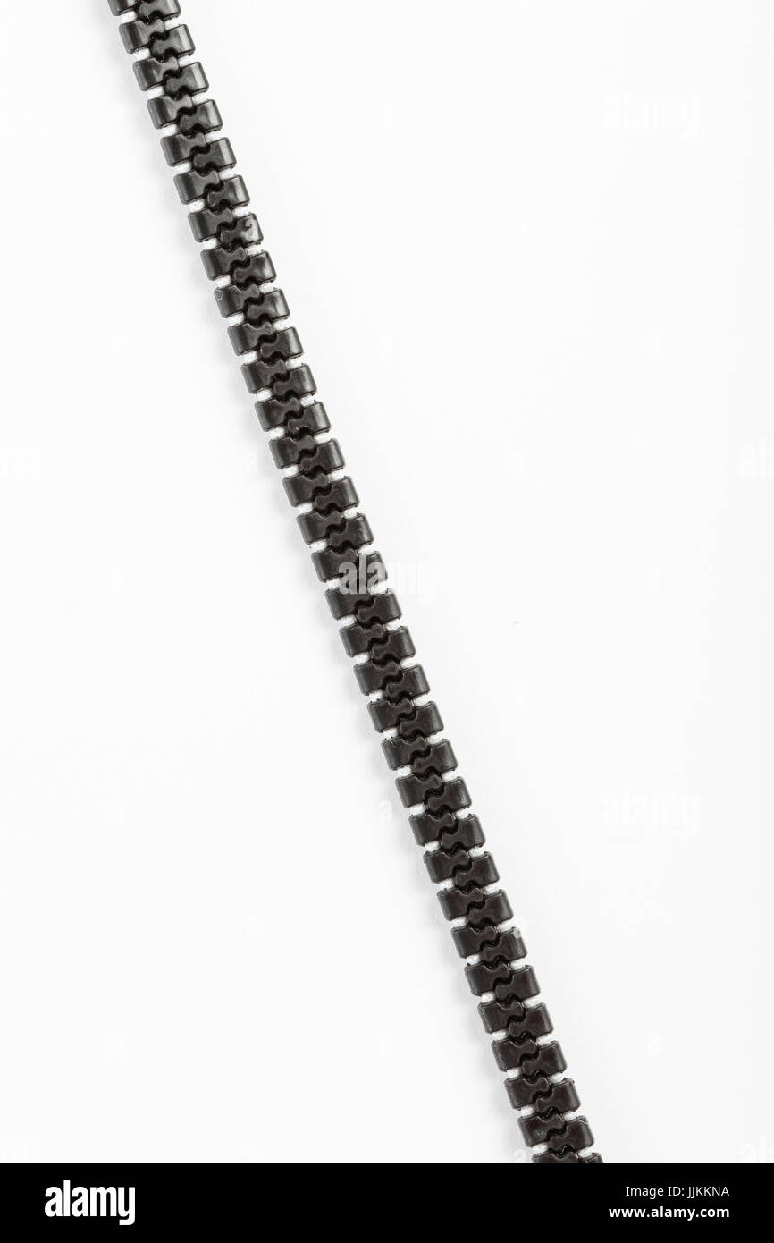 black plastic zipper with white background and copy space. - Stock Image