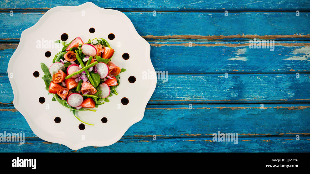 Fresh salad in white plate on blue table - Stock Image