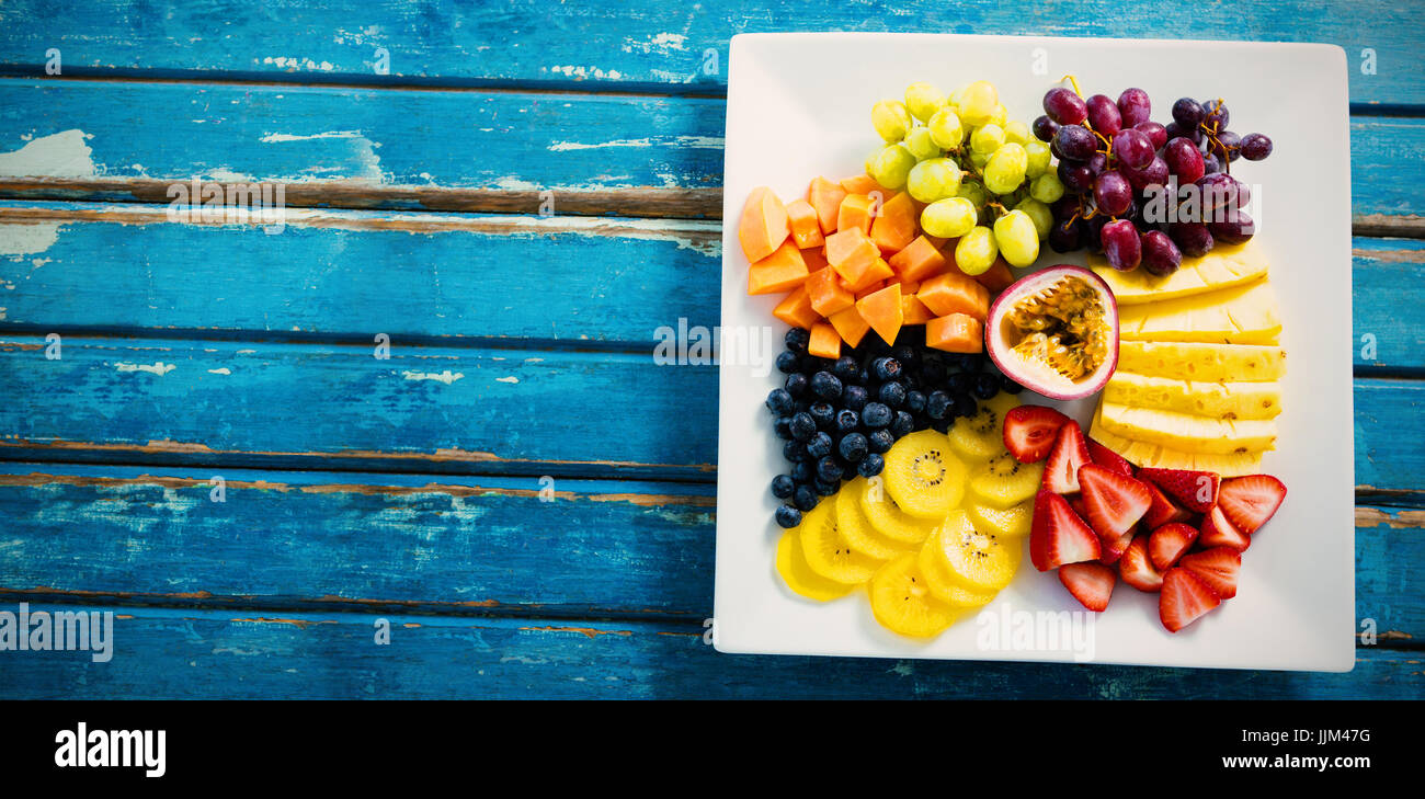 Fresh fruits in white plate on blue table - Stock Image