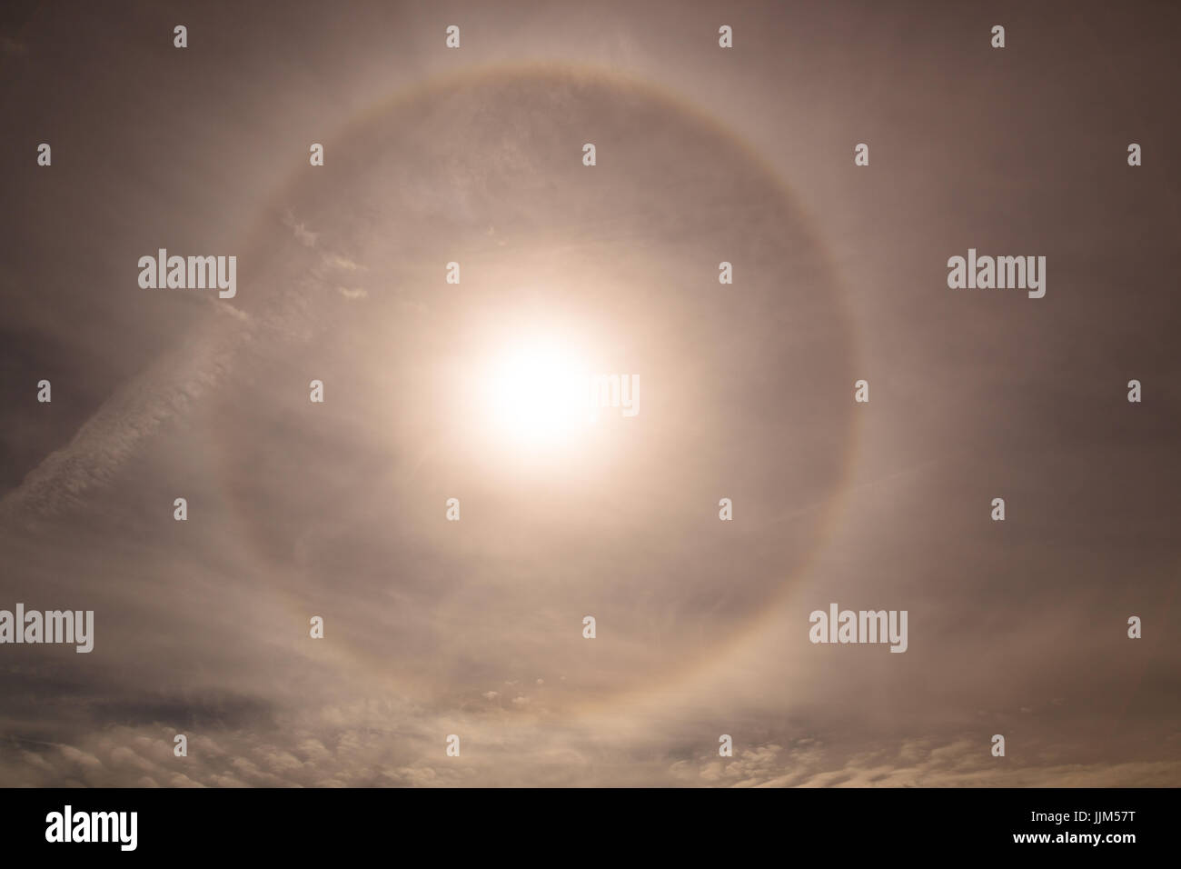 A strange refraction phenomenon around the sun with vapor trails crossing the sky. - Stock Image