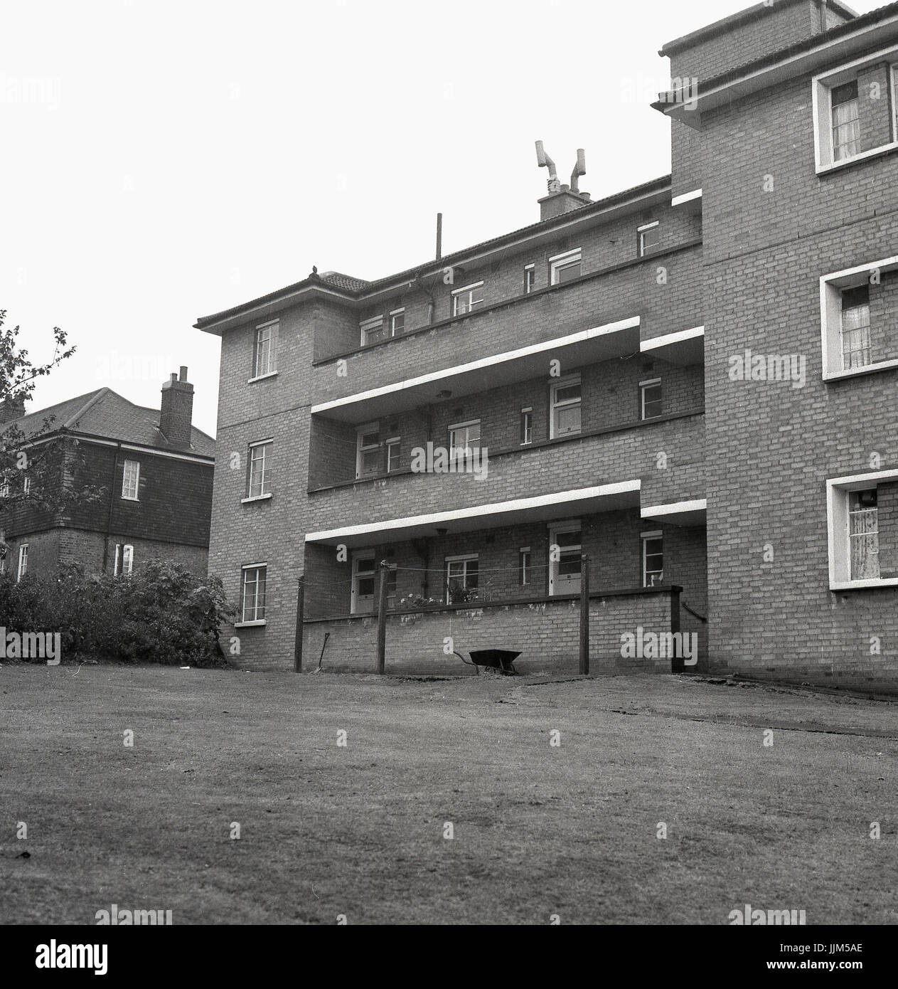 1972, exterior view from the back of a low-rise three story block of council flats of brick costruction with chimneys - Stock Image