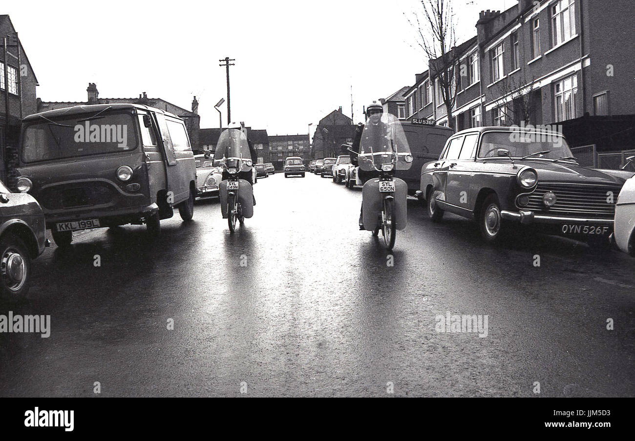 1974, South London, two female traffic wardens on patrol ride down a street of parked cars and vans on their new - Stock Image