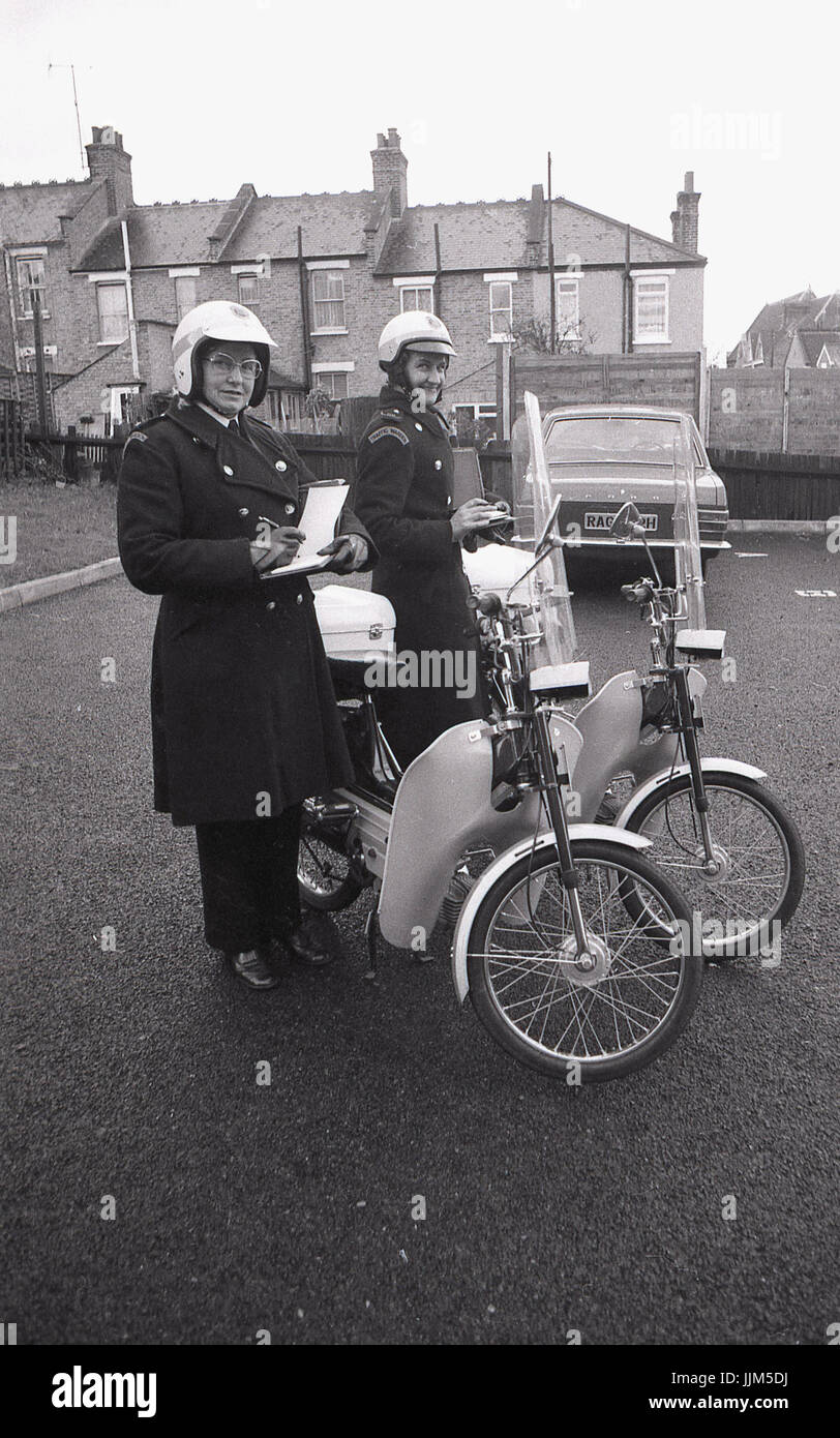 1974, South London, two female traffic wardens out on patrol with their ticket books and their new mode of  transport - Stock Image