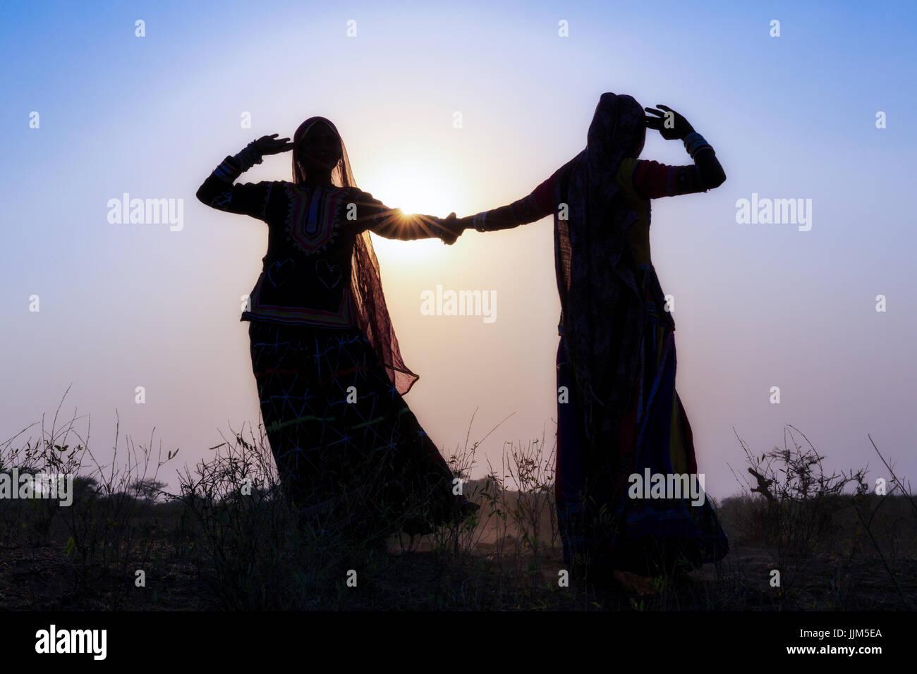 Two gypsy women in dresses dancing in front of the setting sun, Pushkar Camel Fair, Pushkar, Rajasthan, India - Stock Image