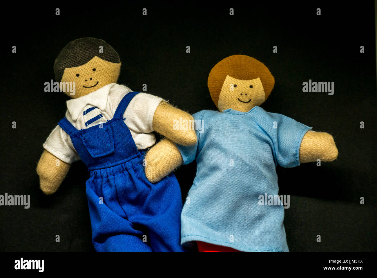 Still life of male and female toy dolls against black background to represent parents, couple, family members, relationships, - Stock Image