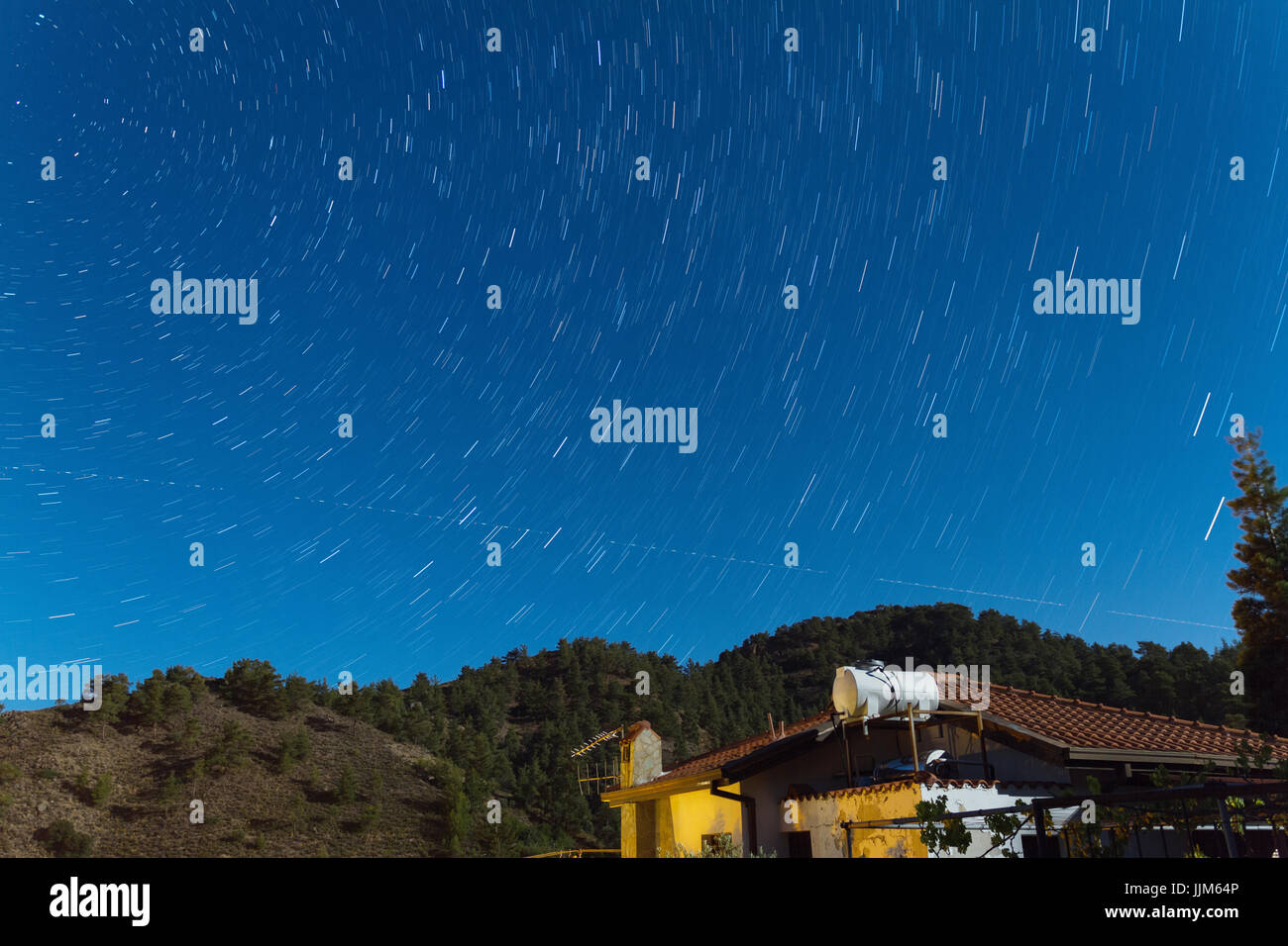 Star Trails over a house at the Troodos mountains as an aeroplane traverses the sky. Captured over Kakopetria village - Stock Image