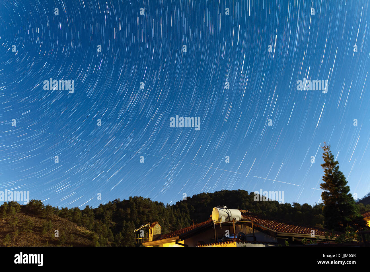 Star Trails over a house at the Troodos mountains as two aeroplanes travers the sky. Captured over Kakopetria village - Stock Image
