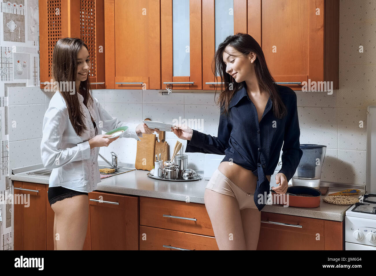 Two sisters talking in the kitchen while washing dishes ...