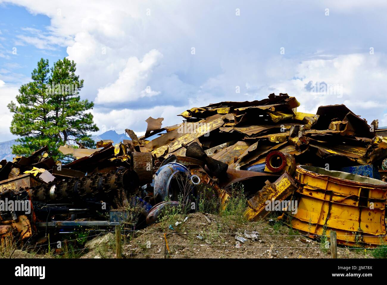 Colorful scrap metal in junk yard against a natural landscape - Stock Image