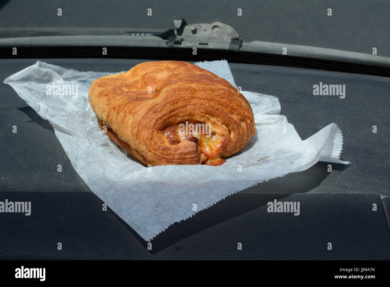 Breakfast on the go of bakery ham and Swiss cheese croissant on automobile dashboard - Stock Image