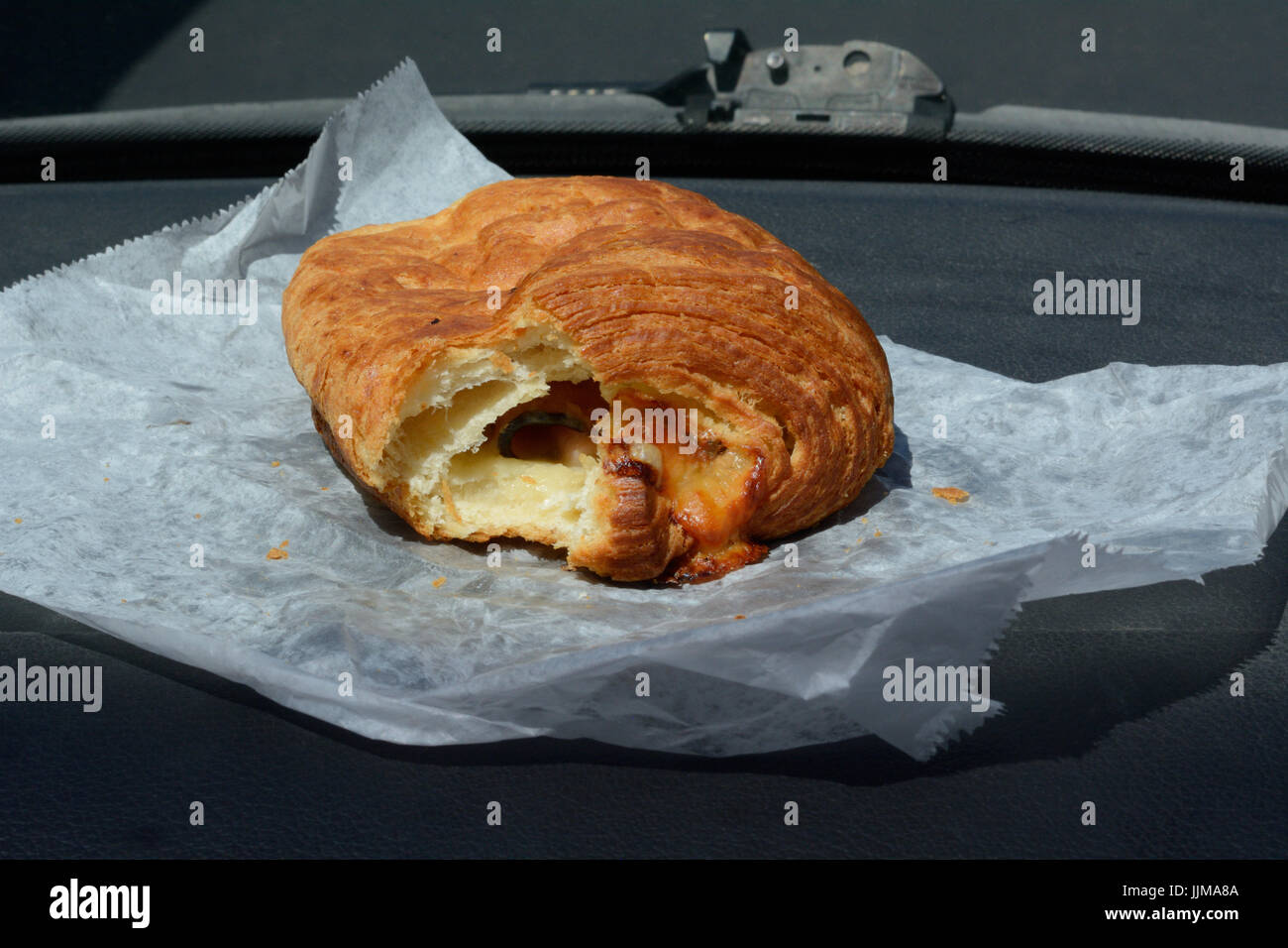 Breakfast on the go of partially eaten bakery ham and Swiss cheese croissant on automobile dashboard - Stock Image