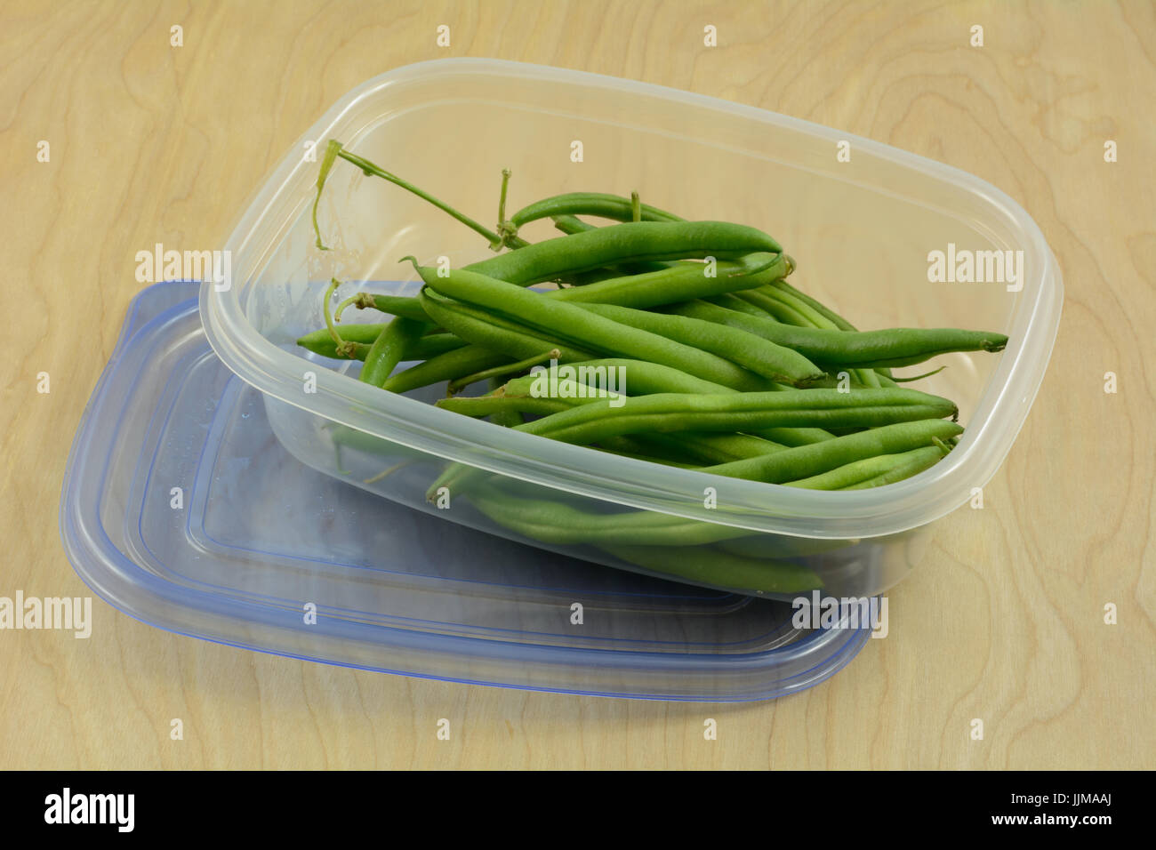 Raw green string beans in plastic refrigerator storage container