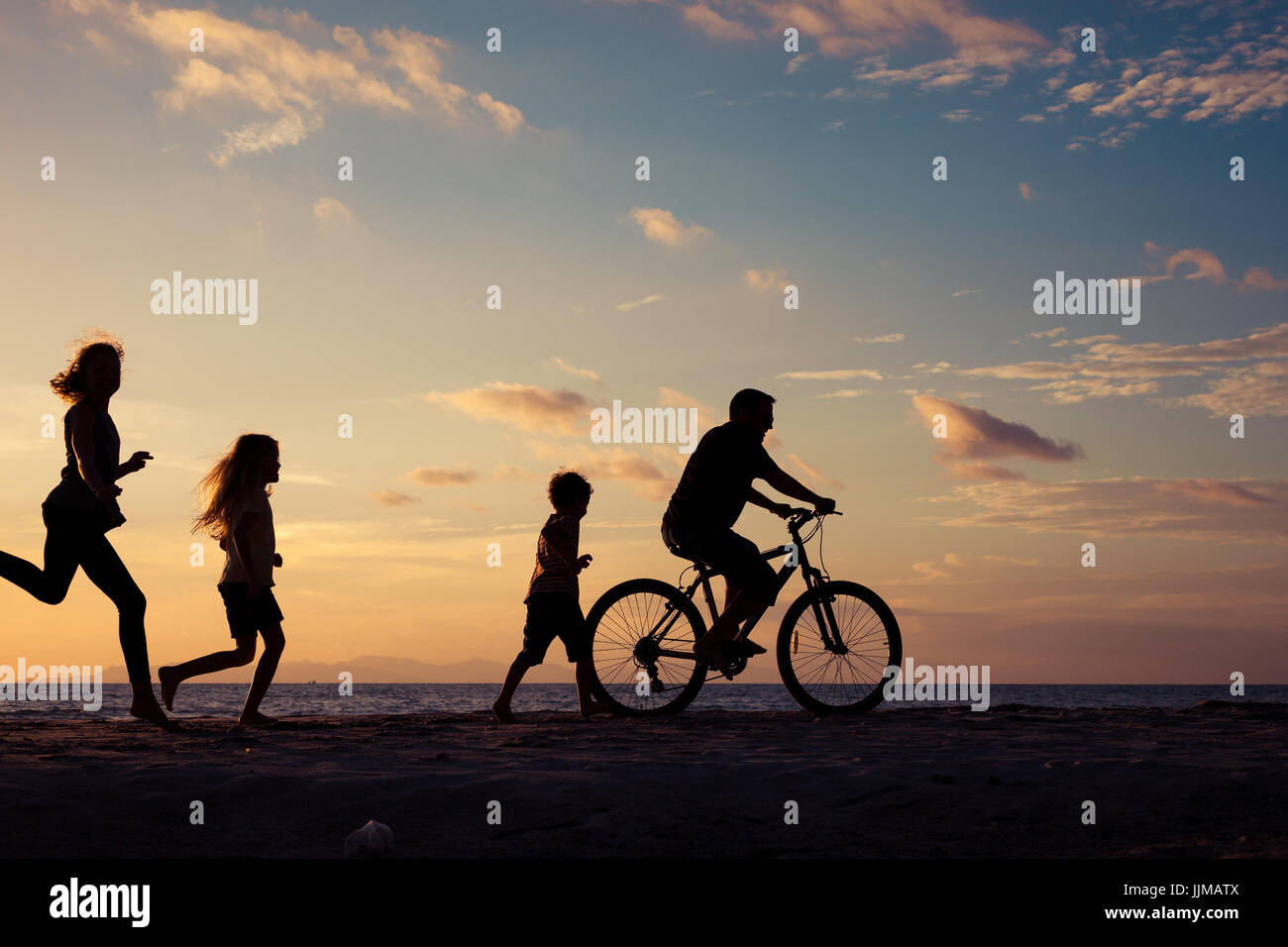 Father and children playing on the beach at the sunset time. Concept of friendly family. - Stock Image
