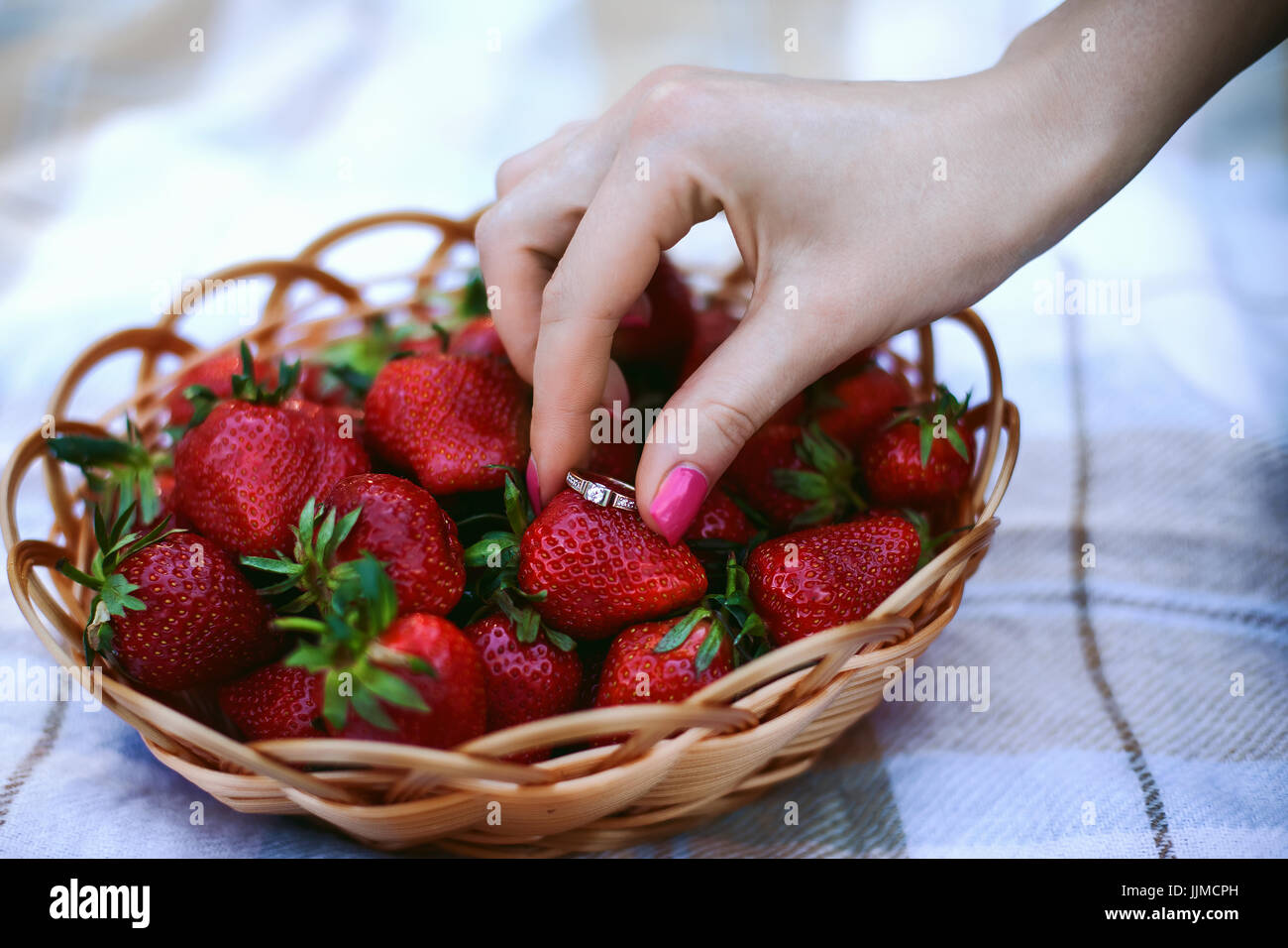 The girl's hand holds an engagement ring near a wicker basket with strawberries. Still life. concept of Betrothal, - Stock Image