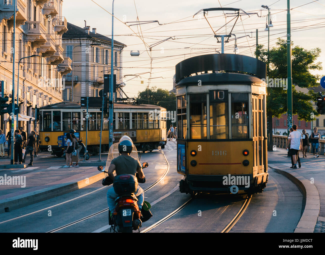 Traditional yellow tram near city centre, Milan, Lombardy, Italy - Stock Image