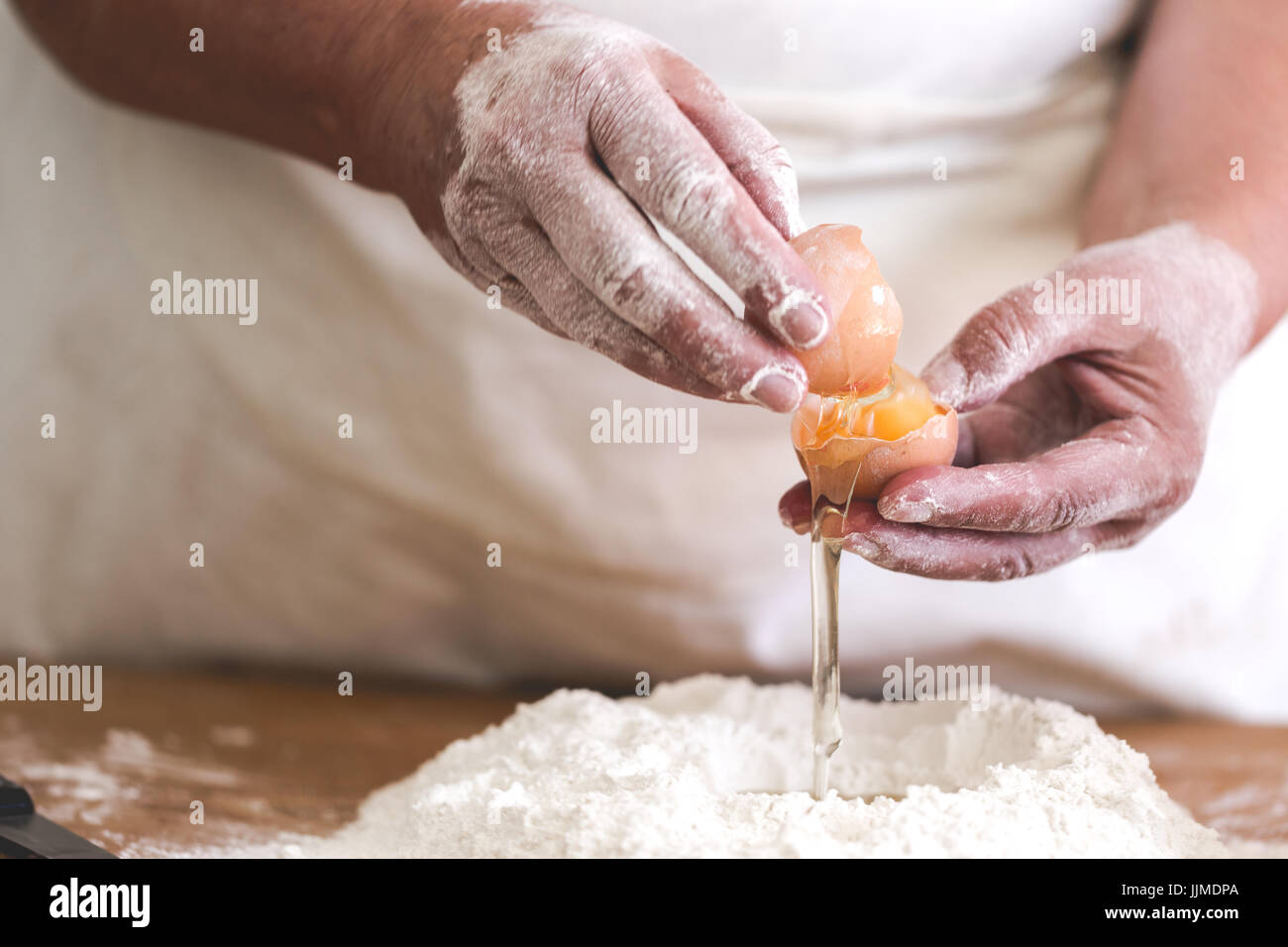 Senior woman adding egg to pastry. Focus on broken egg and old working hands. Horizontal orientation, saturated - Stock Image