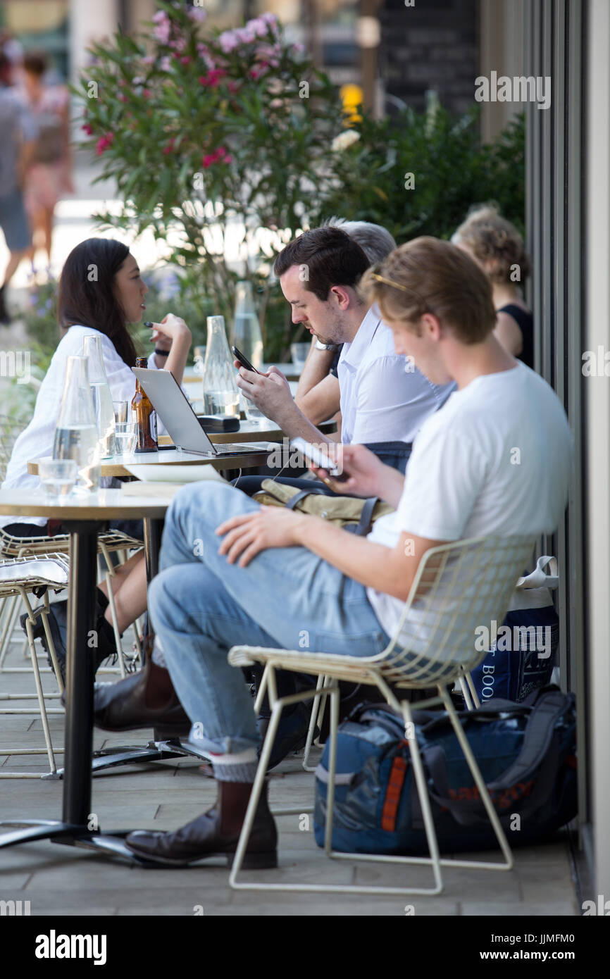 People sitting outside a cafe talking, using phones and laptops. Taken around Granary Square, Kings Cross, London - Stock Image