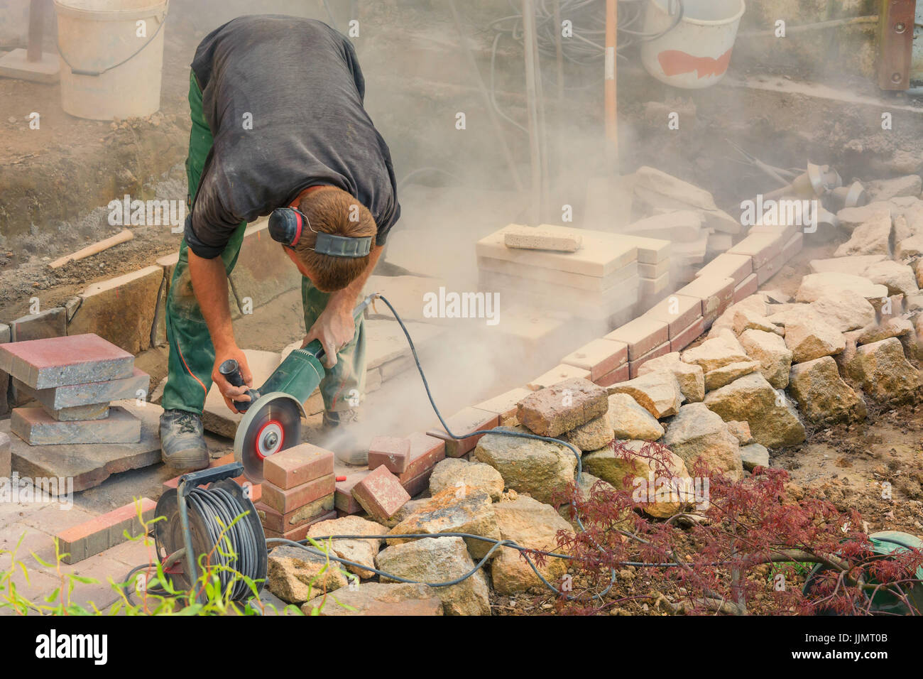 Man cutting stone slabs, concrete slab with an electric grinder - Stock Image