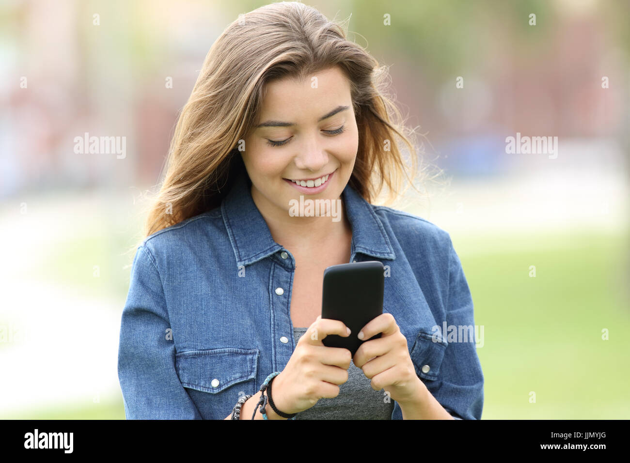 Portrait of a happy teen walking and reading text in a smart phone in the street - Stock Image