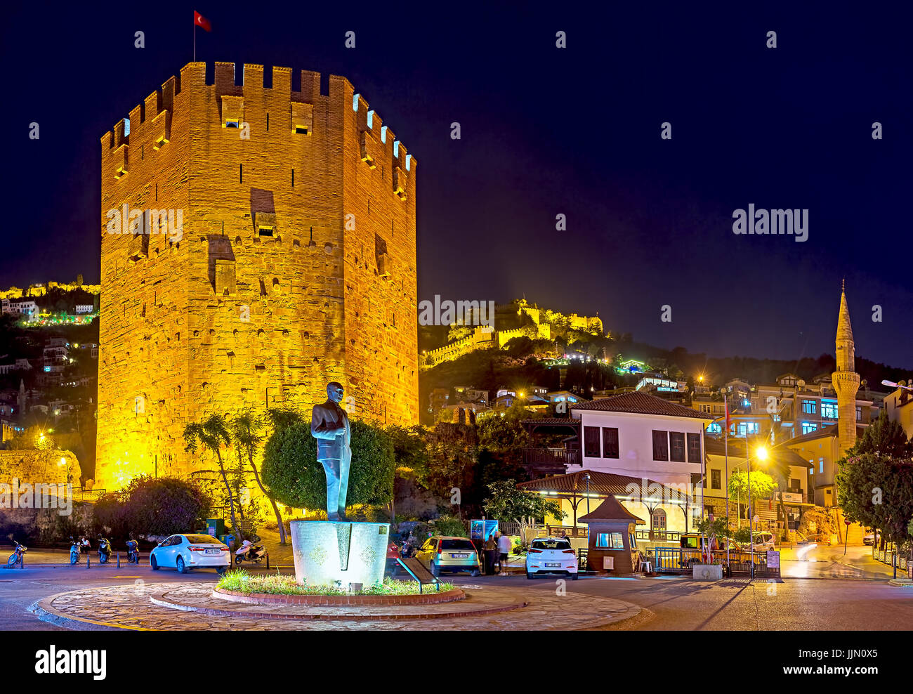 The night cityscape of Alanya, the Red Tower (Kizil Kule) and ramparts of the Citadel are brightly illuminated, - Stock Image