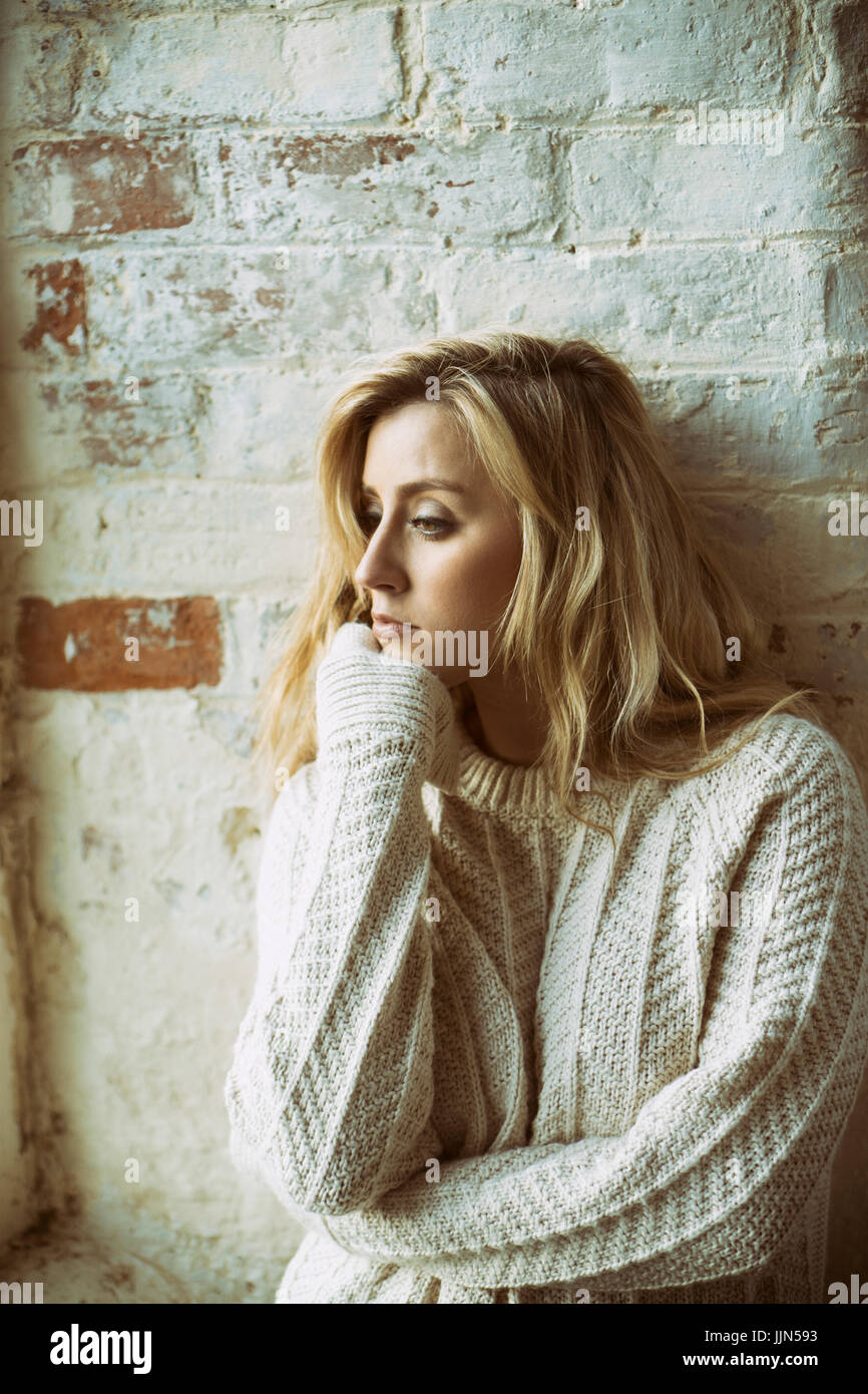 Sad young blond woman looking away - Stock Image