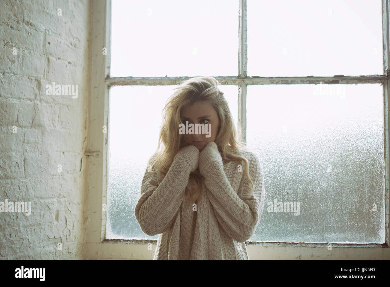 Scared young woman wearing a wool jumper standing by the window looking away - Stock Image