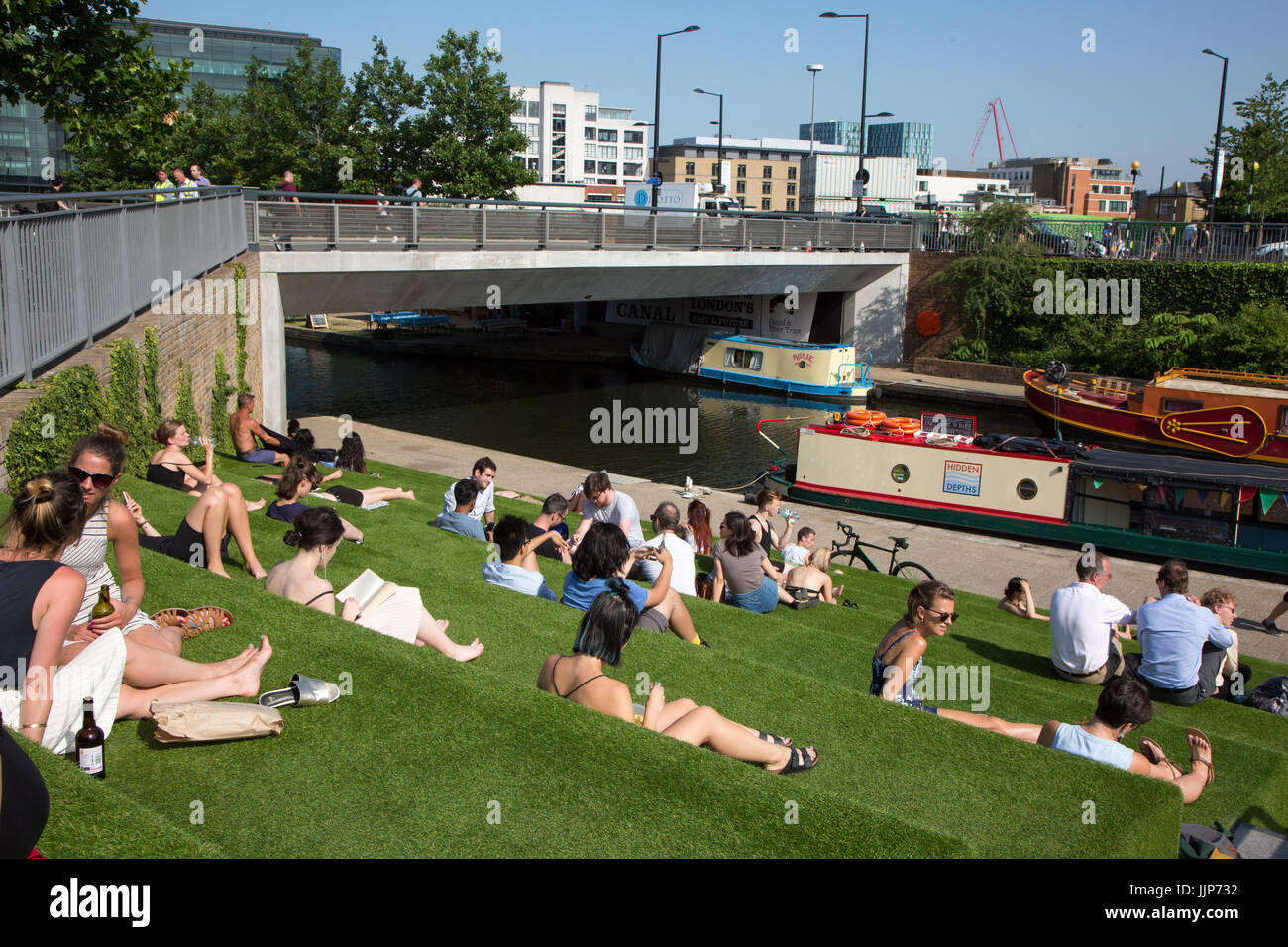 Young Londoners soak up the sun in a seating area outside Granary Square, Kings Cross, and next to the Grand Union - Stock Image