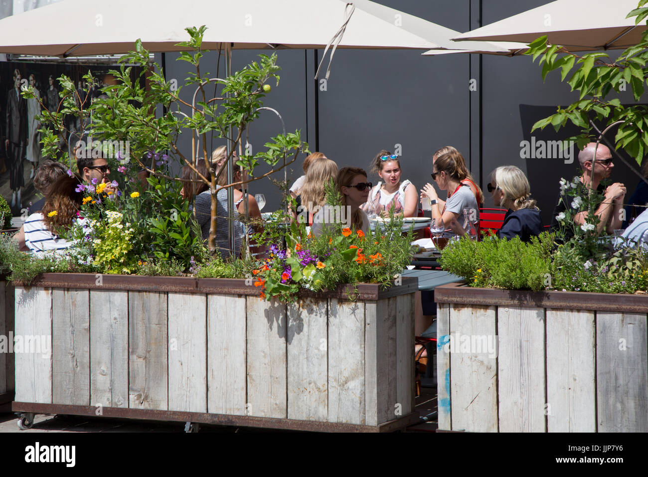 Grain Store, a restaurant in Granary Square King's Cross. Diners are eating al fresco in the garden outside - Stock Image