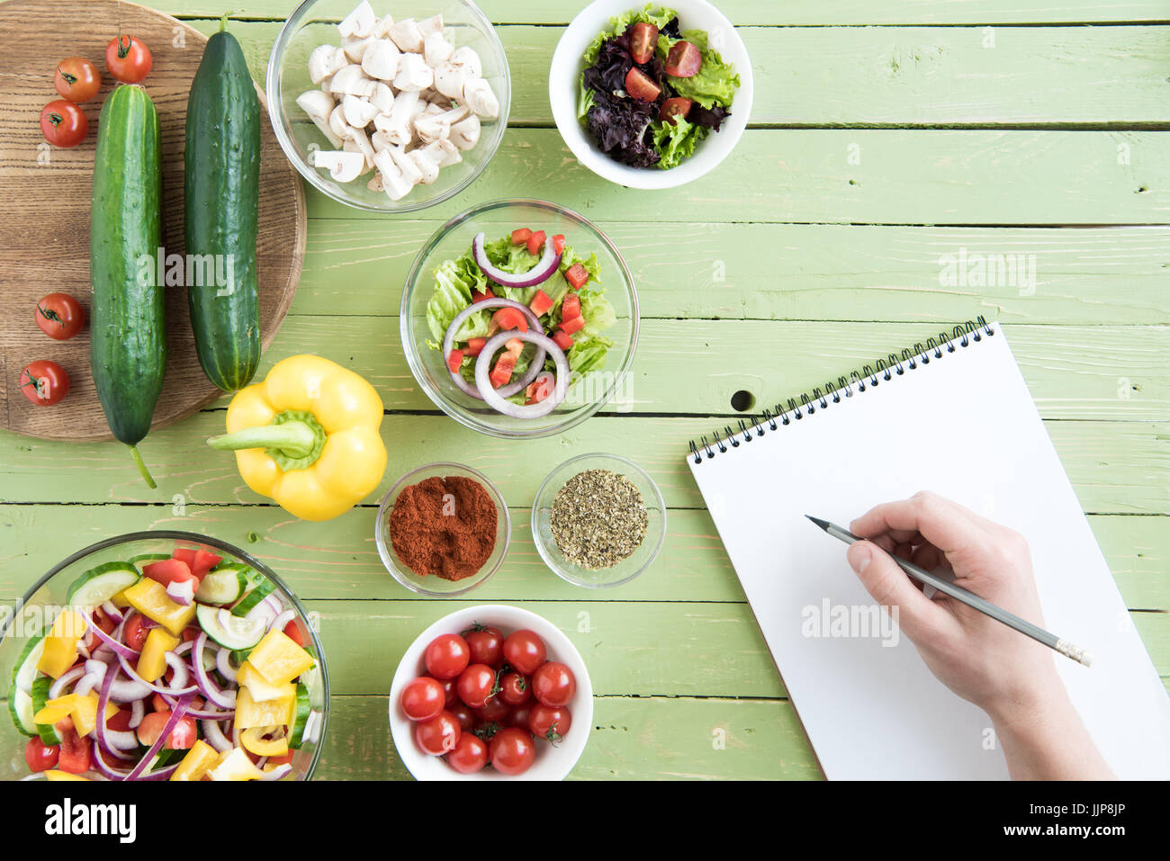 Close-up partial view of person holding pencil and writing recipe in cookbook while cooking - Stock Image
