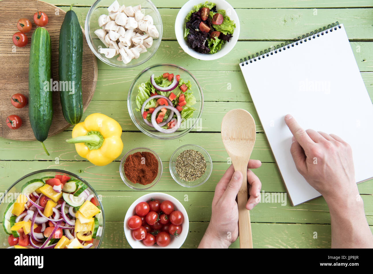 Close-up partial view of person holding wooden spoon and pointing at recipe in cookbook while cooking - Stock Image