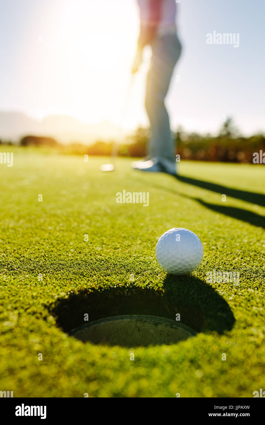 Golf ball at the edge of hole with player in background. Professional golfer putting ball into the hole on a sunny - Stock Image