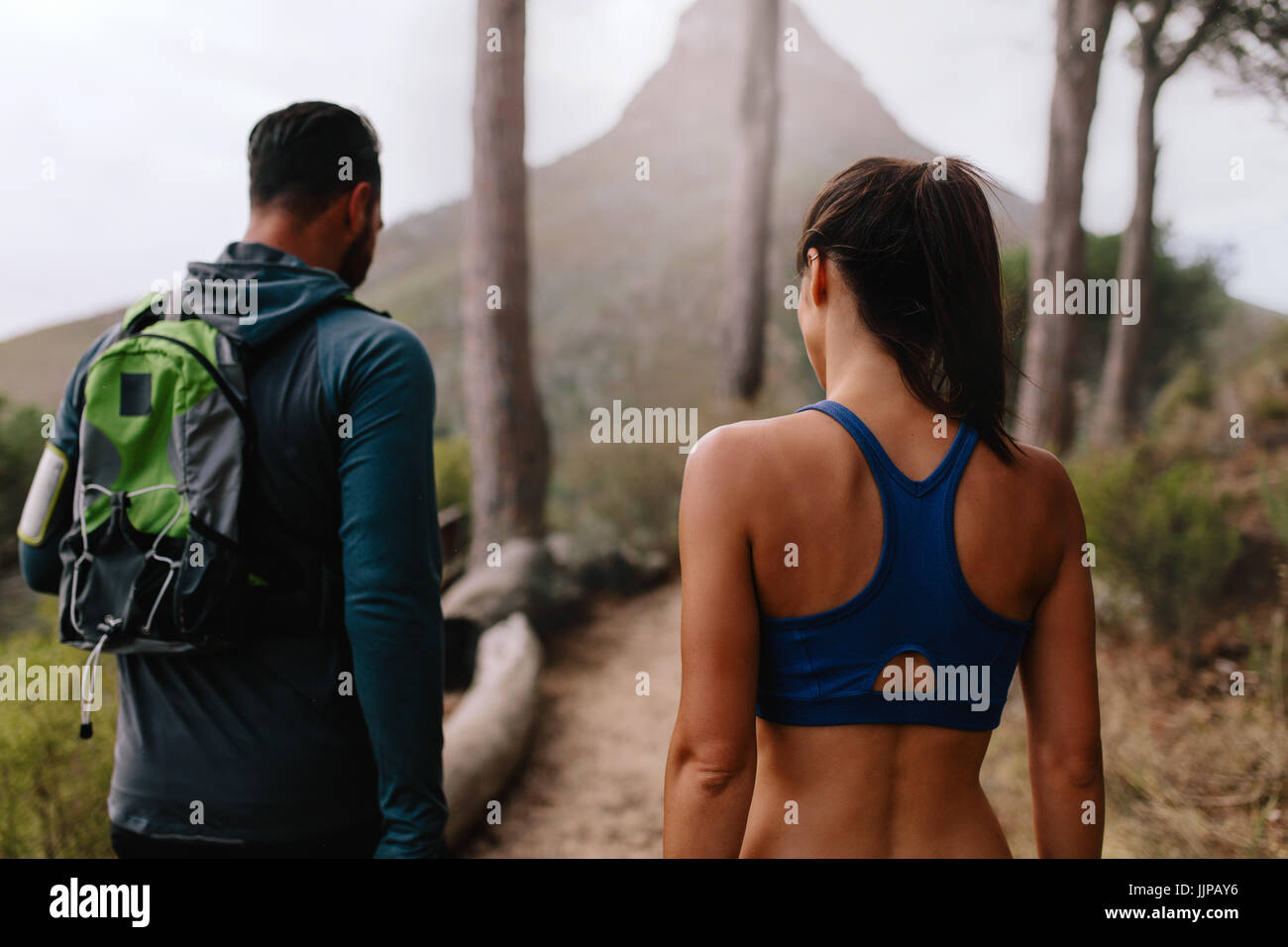 Rear view shot of healthy young couple walk through mountain trail. Young man and woman walking through country - Stock Image