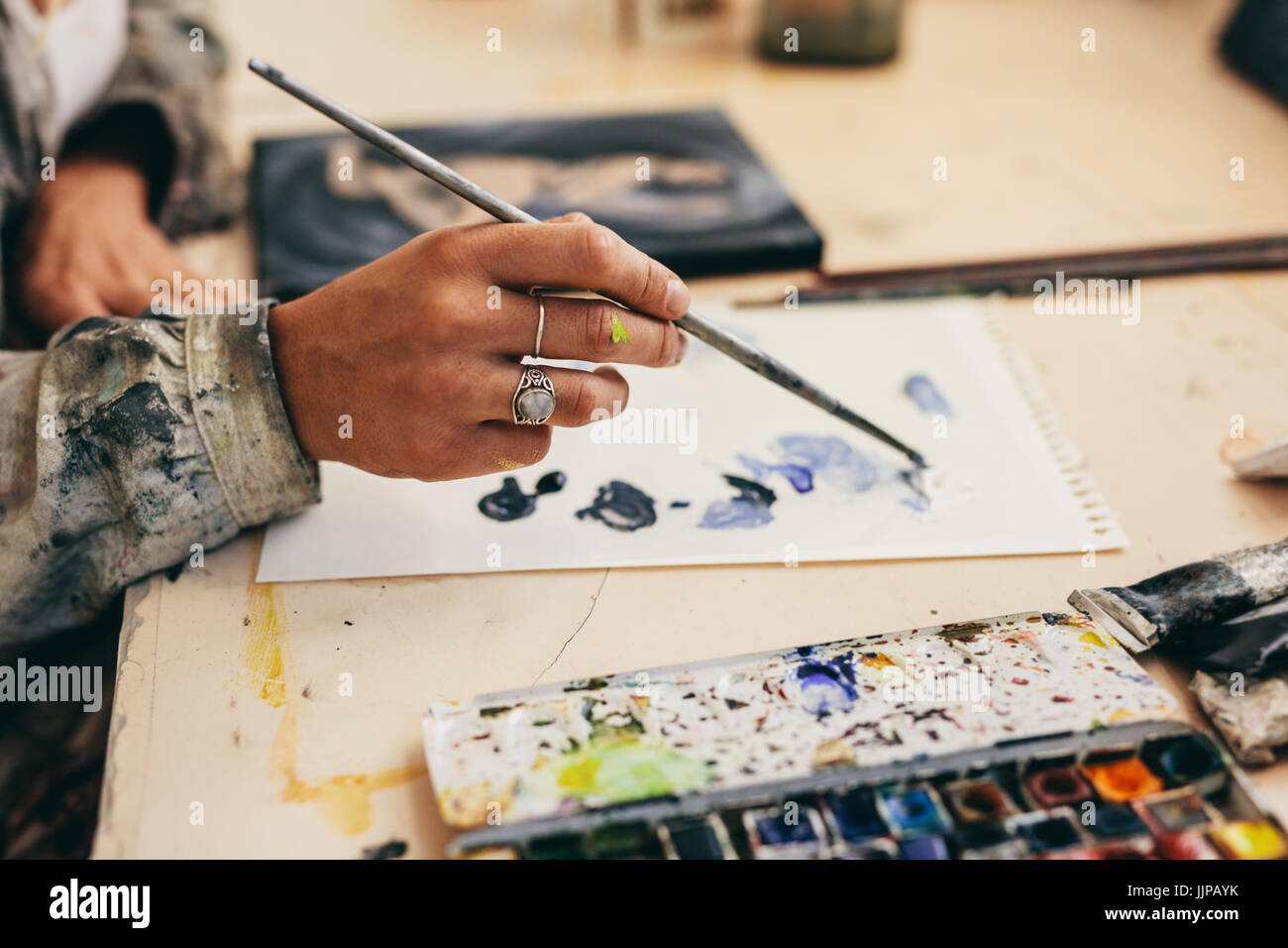 Close up of female artist's hand holding brush and mixing colors on paper. Cropped shot of woman painter working - Stock Image