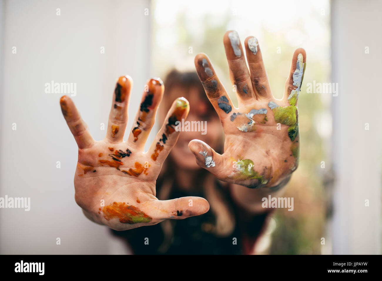 Close up of female artist showing her messy hands. Focus on hands of woman painter with color. - Stock Image