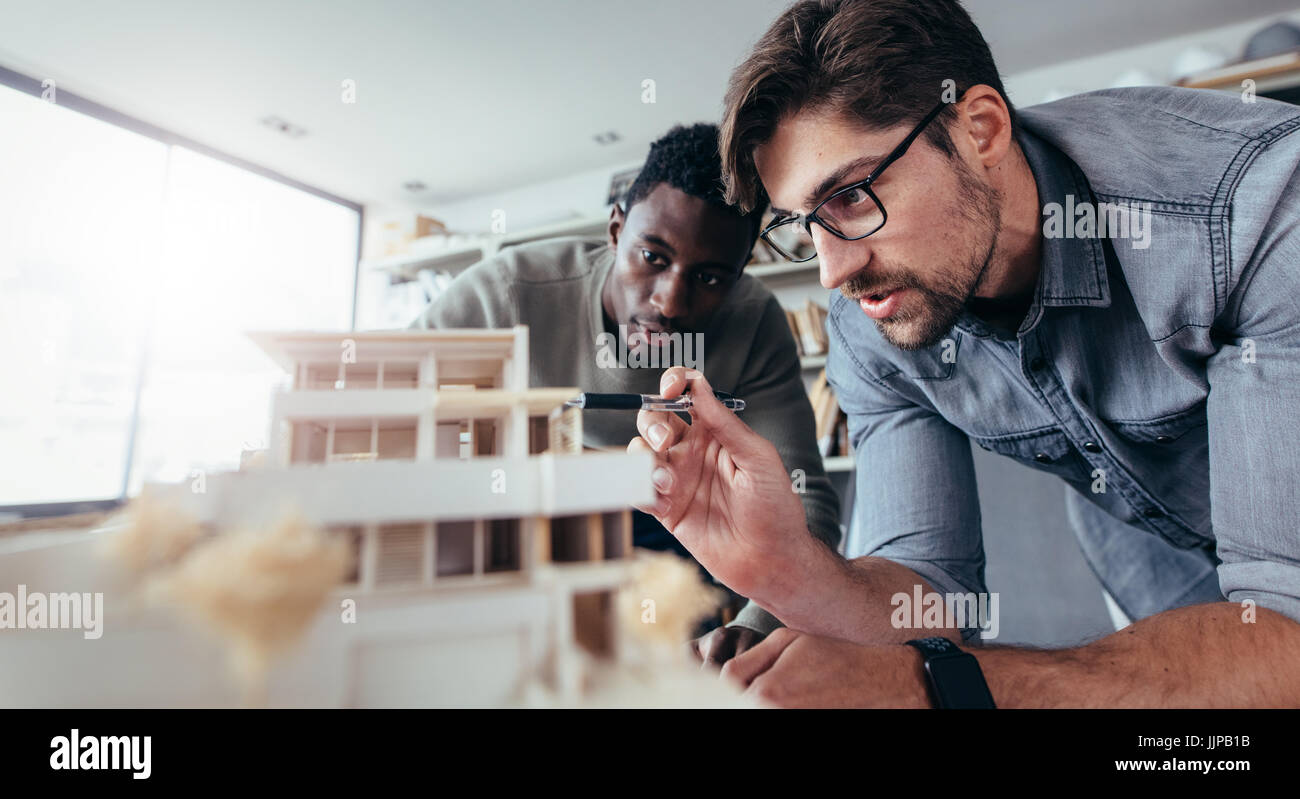Two male architects in office discussing over house model. Architect working on an architectural model. - Stock Image