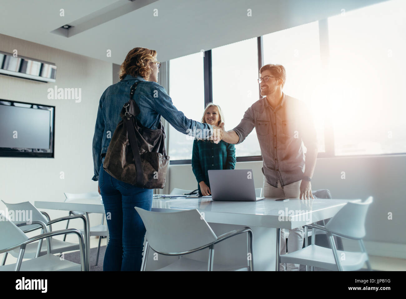 Business people finishing up a meeting. Man shaking hands with female client after successful deal. - Stock Image